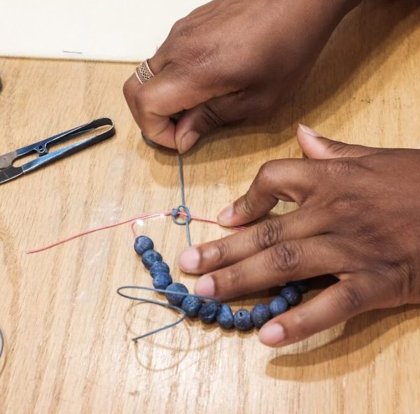 A student at Beadworks during a macrame class using druzy gemstone beads
